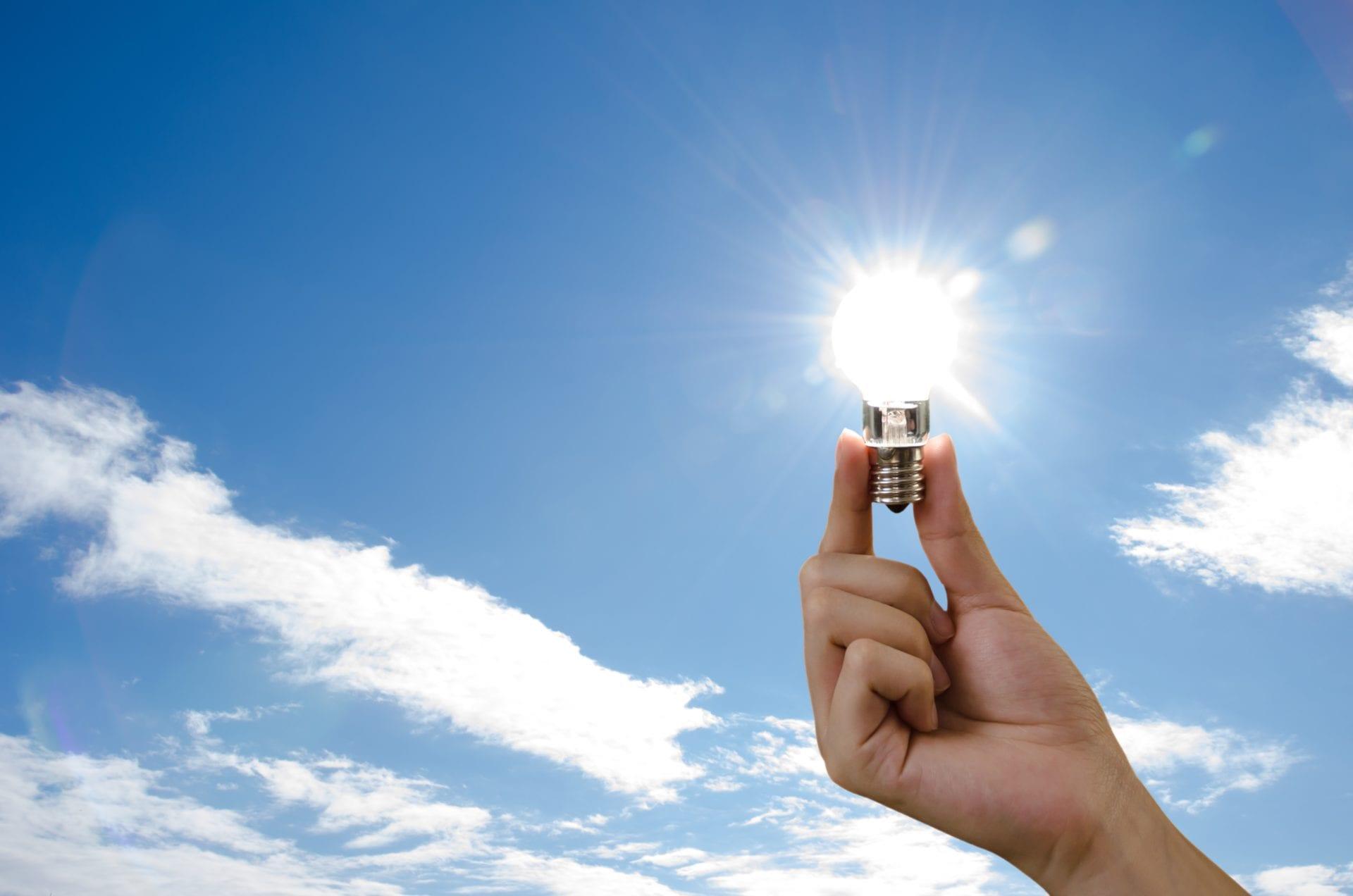 Female hand holding light bulb over the sun.